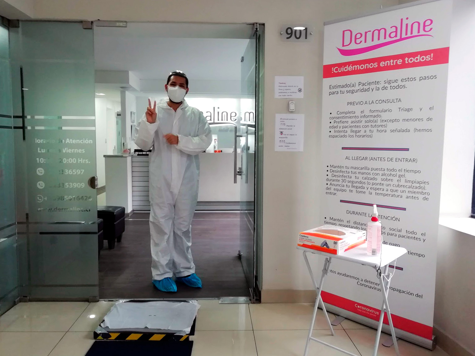 A dentist in his personal protective equipment greets at the entrance to a clinic during the quarantine