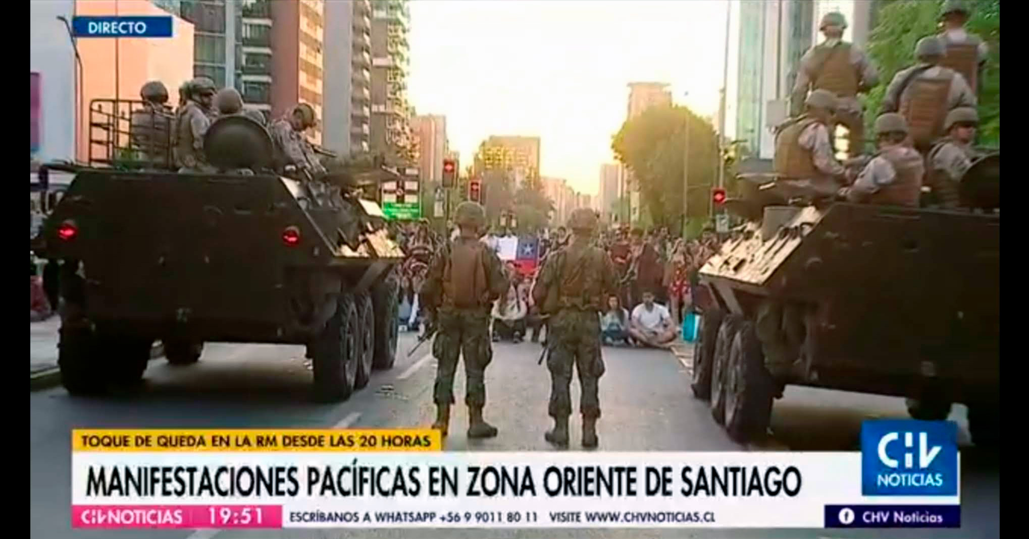 A military group and two tanks in front of a pacific protest