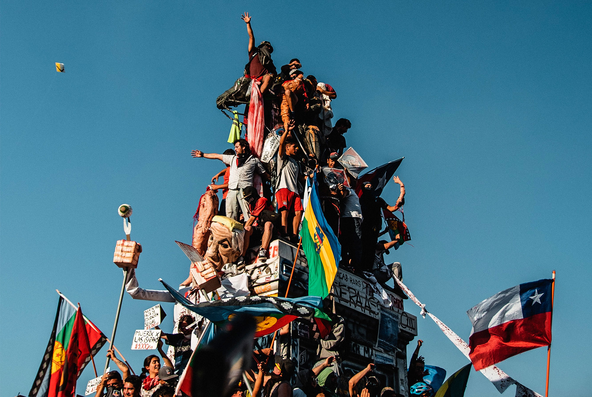 Protesters at the top of a monument at the central square in Santiago